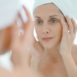 portrait of woman in bathroom applying moisturizing cream