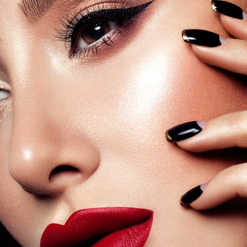 Closeup of woman with red lipstick and black fingernails.