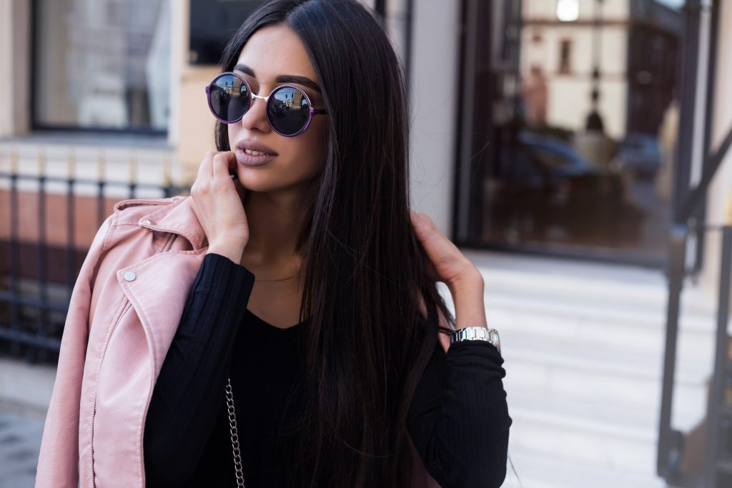 Woman with black sunglasses holding a pink jacket while posing for the camera.