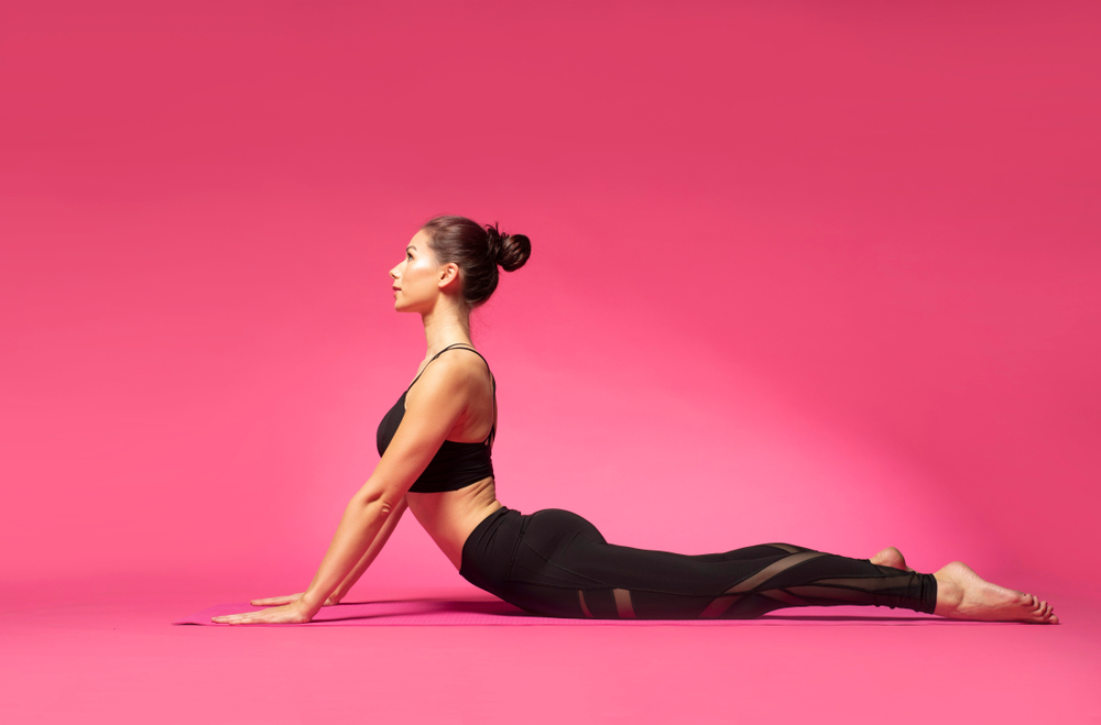 Woman practicing pilates in a bright pink studio.
