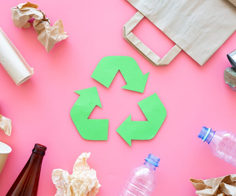 Recyclable material in a circle around recycle sign on top of a pink background.