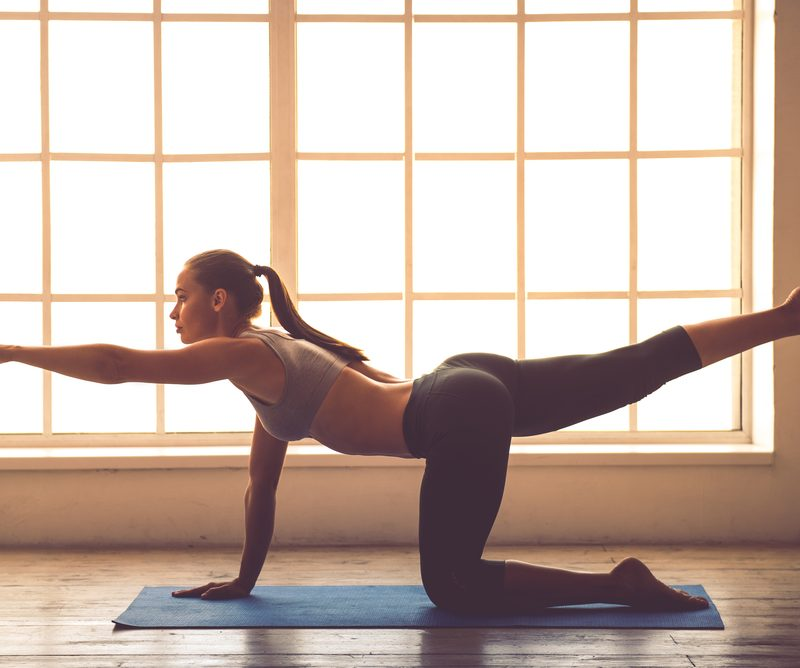Woman exercising on a floor mat in front of large windows.