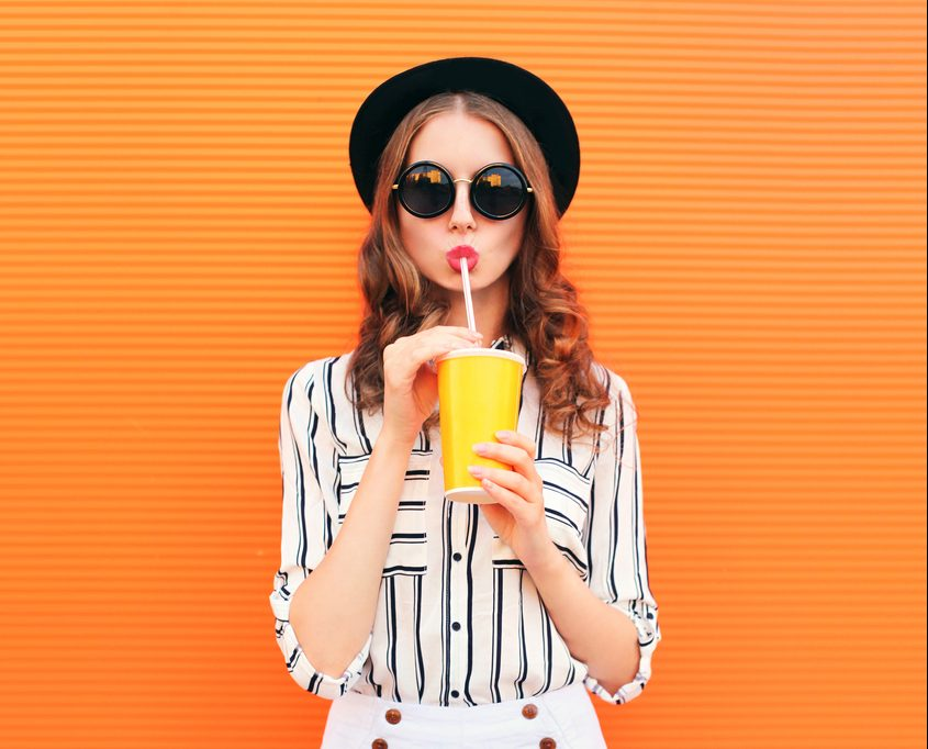 Woman in hat and sunglasses drinking from a cup with a straw.