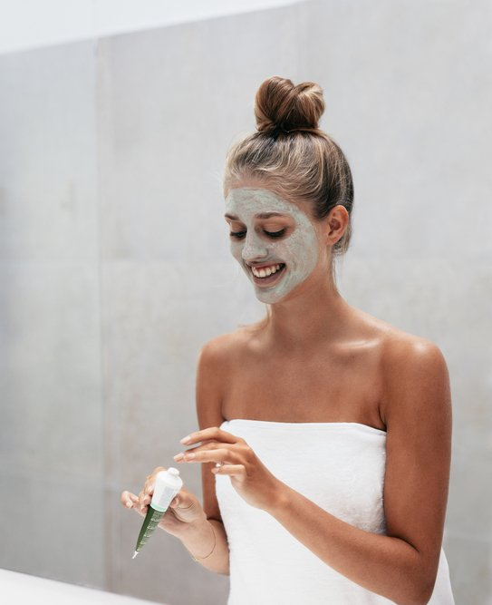 Woman applying a face mask in the bathroom.