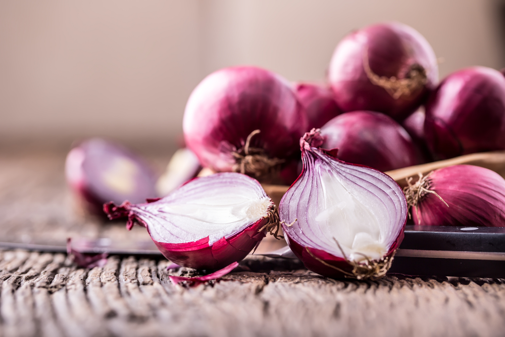Red onions atop a wooden platform.