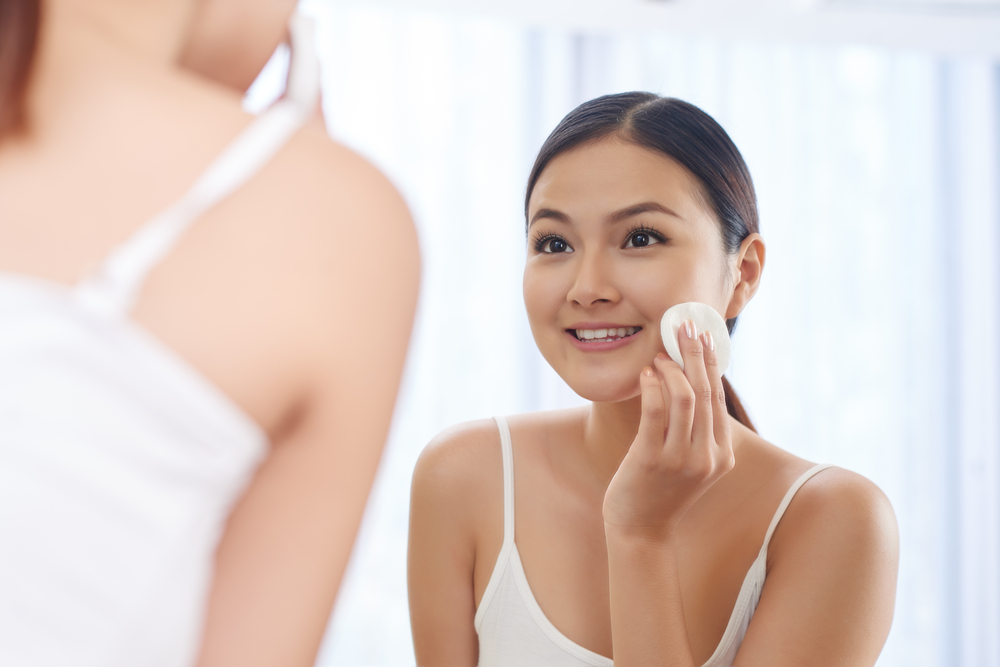 Woman applying toner to her face.