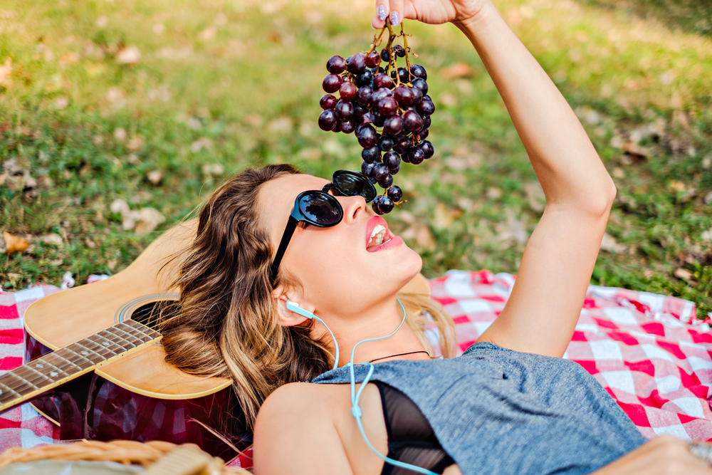 Woman eating grapes outoors at a picnic.