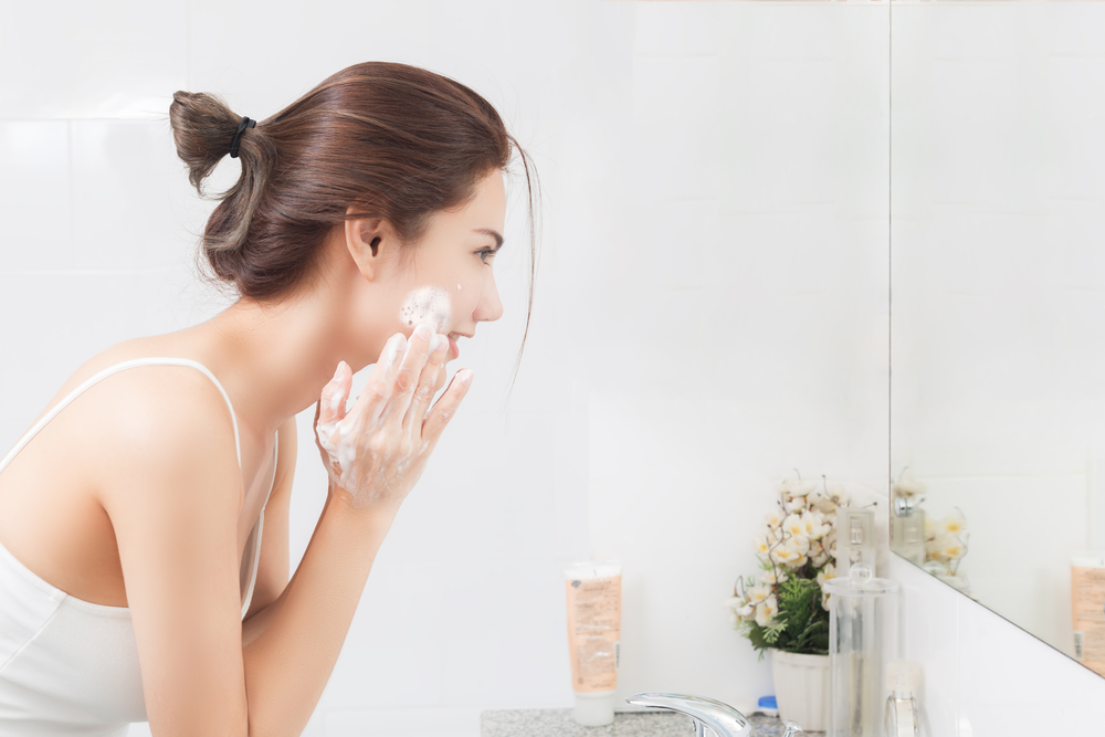 Woman cleansing her face in the bathroom.