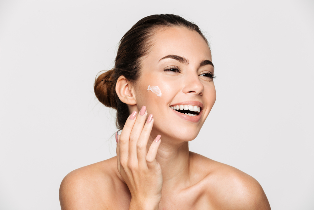 Woman smiling and applying beauty product to her face.
