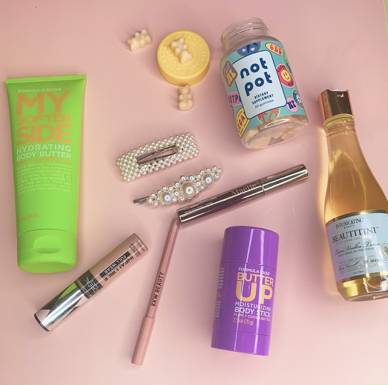 Beauty products on top of a pink background.