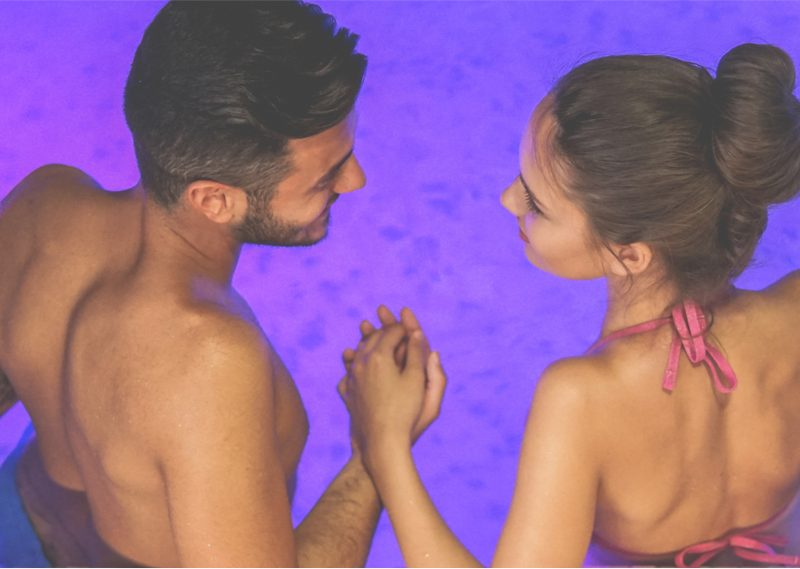 Couple enjoying their time in a spa pool with underwater purple lights.