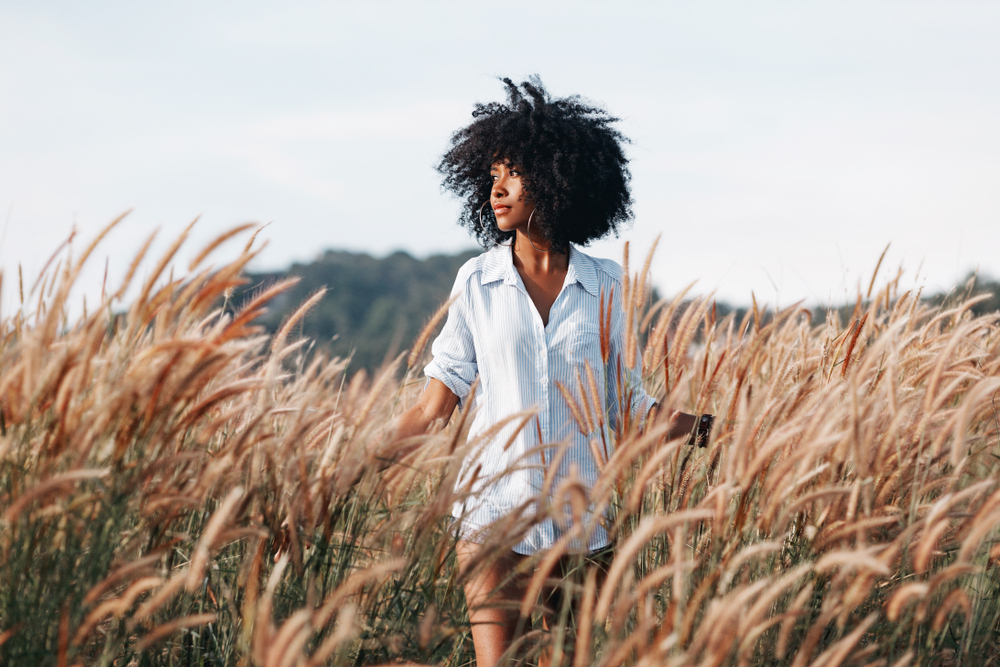 African American woman with natural hair roaming a field in a large shirt.