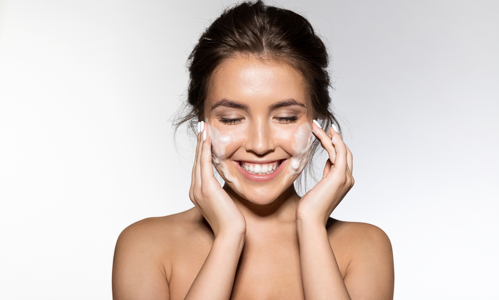 Woman smiling while applying moisturizer to her face.