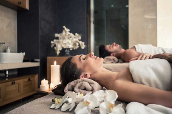 Couple at a spa laying on their backs on a massage table.