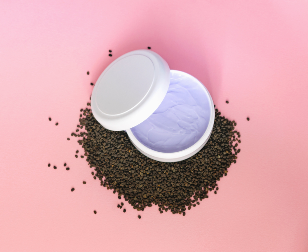 Bakuchiol skin care cream with raw seeds on pink background.