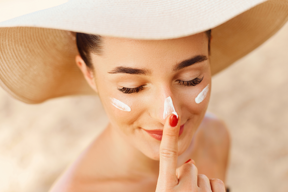 Closeup of woman with large hat smiling as she applies moisturizer to her face.