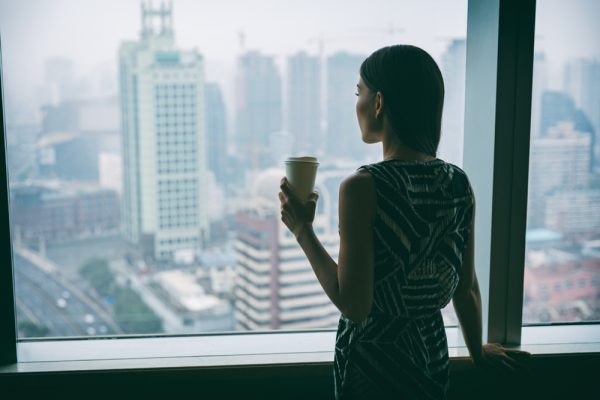 Woman taking break drinking coffee and starting out office window.
