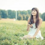 Woman sitting in the grass listening to music while smiling.