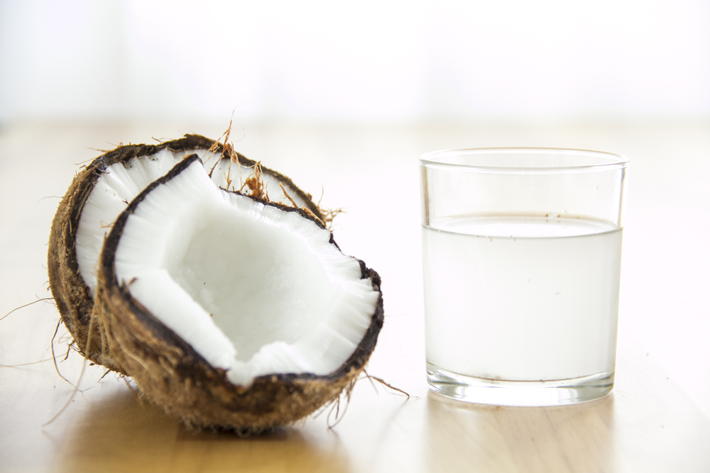 Coconut water in a glass next to a coconut split in half.
