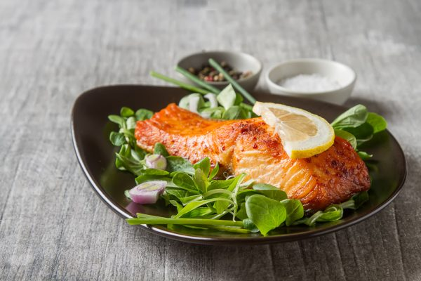 Cooked salmon on a plate with vegatables.