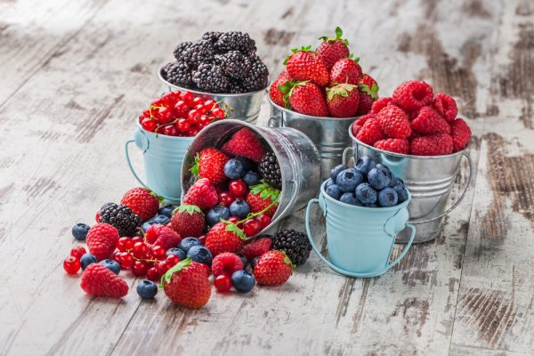 An assortment of several different types of berries in separated buckets.
