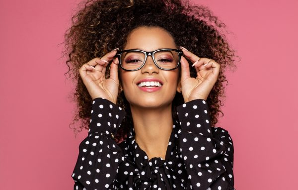 African American woman infront of pink backdrop holding her glasses to her face as she smiles.