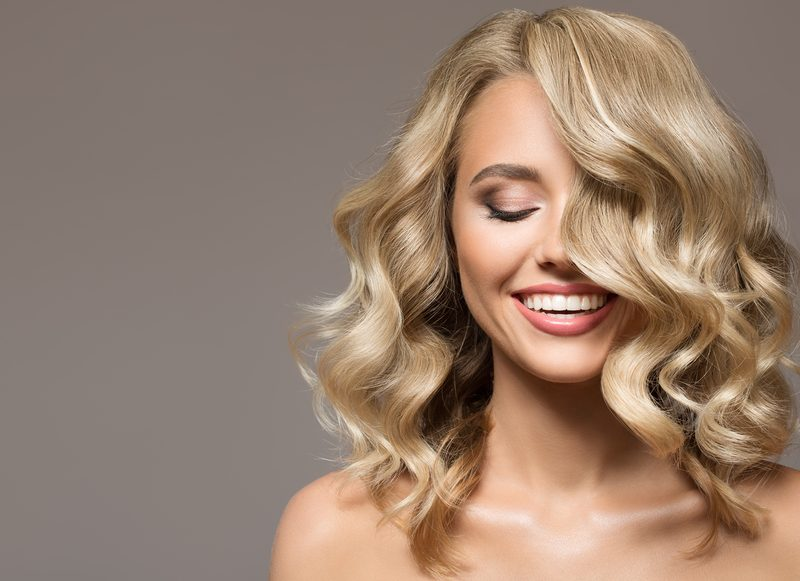 Woman with luxurious blonde hair smiling.