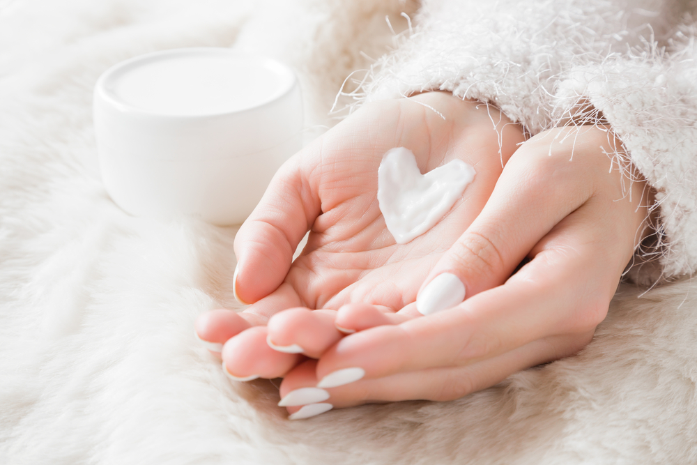 Picture of hands with moisturizer in a heart shape.