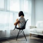 Depressed woman sitting on a chair and staring out of a window.