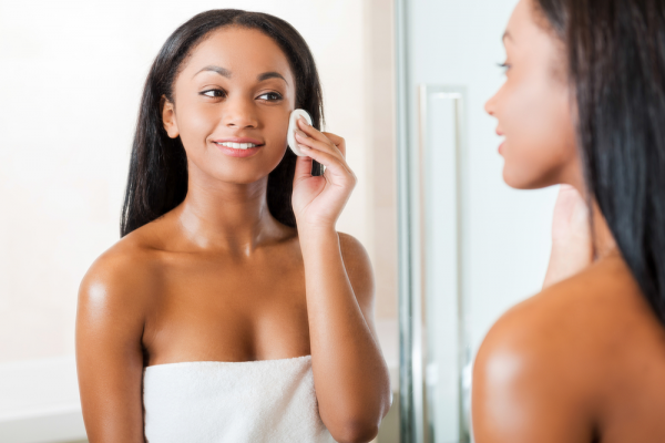Woman applying applying skincare product to her face with cotton pad in the bathroom.
