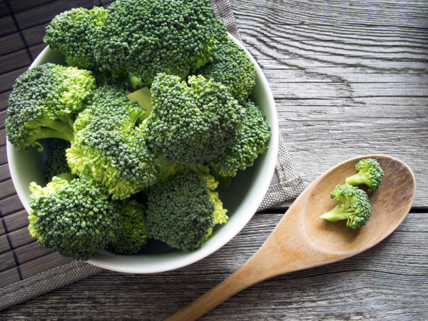 Broccoli in a bowl by a wooden spoon.