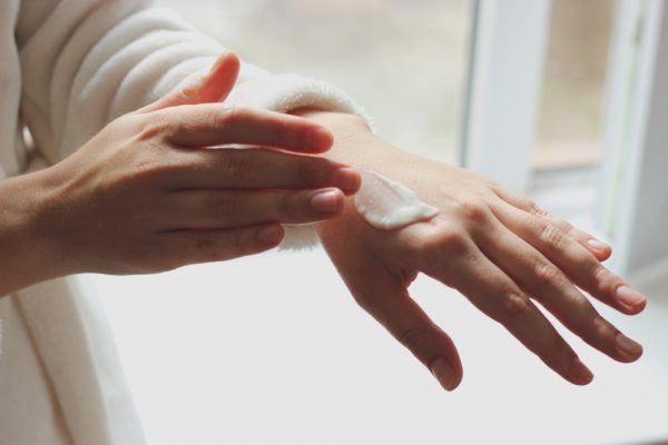 Woman applying moisturizer to her hands.