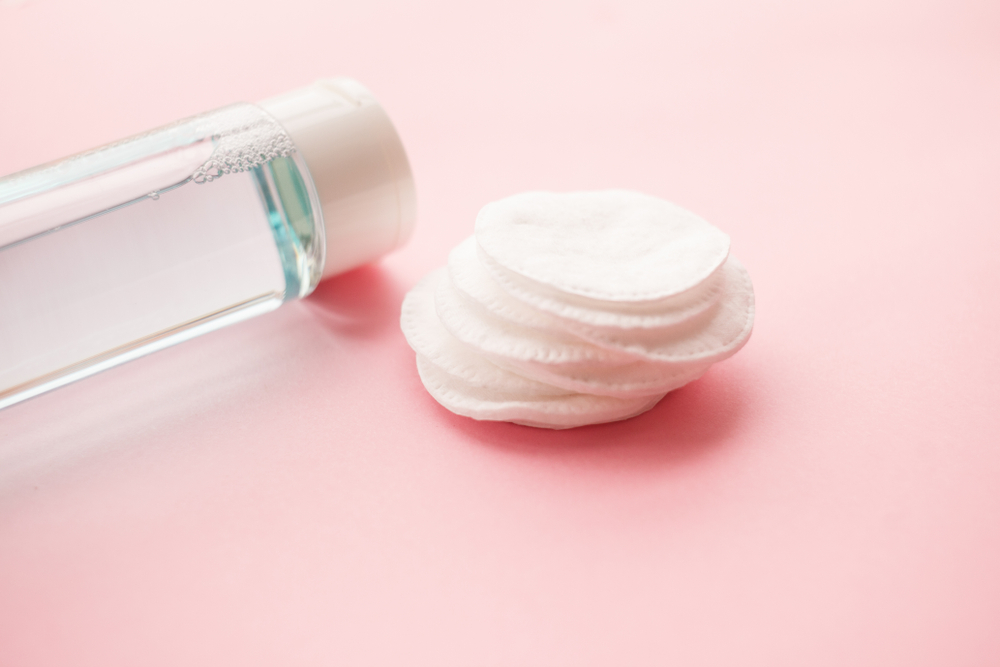 Bottle of skincare product by cotton pads on pink background.