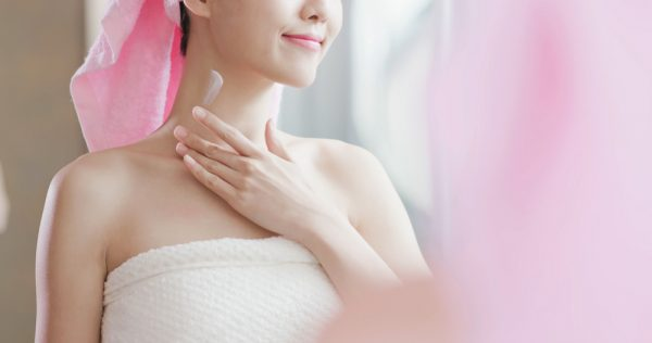 Woman applying moisturizer to her neck.