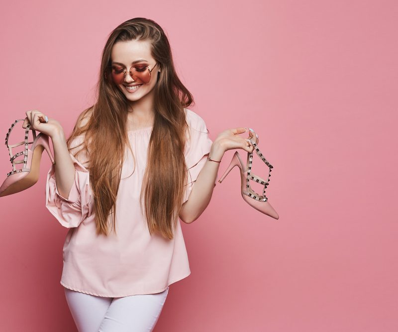 Woman in pink blouse holding her shoes infront of a pink background.