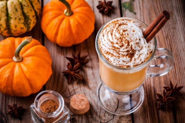 A pumpkin spice latte on top of a table across from pumpkins and pumpkin spice.