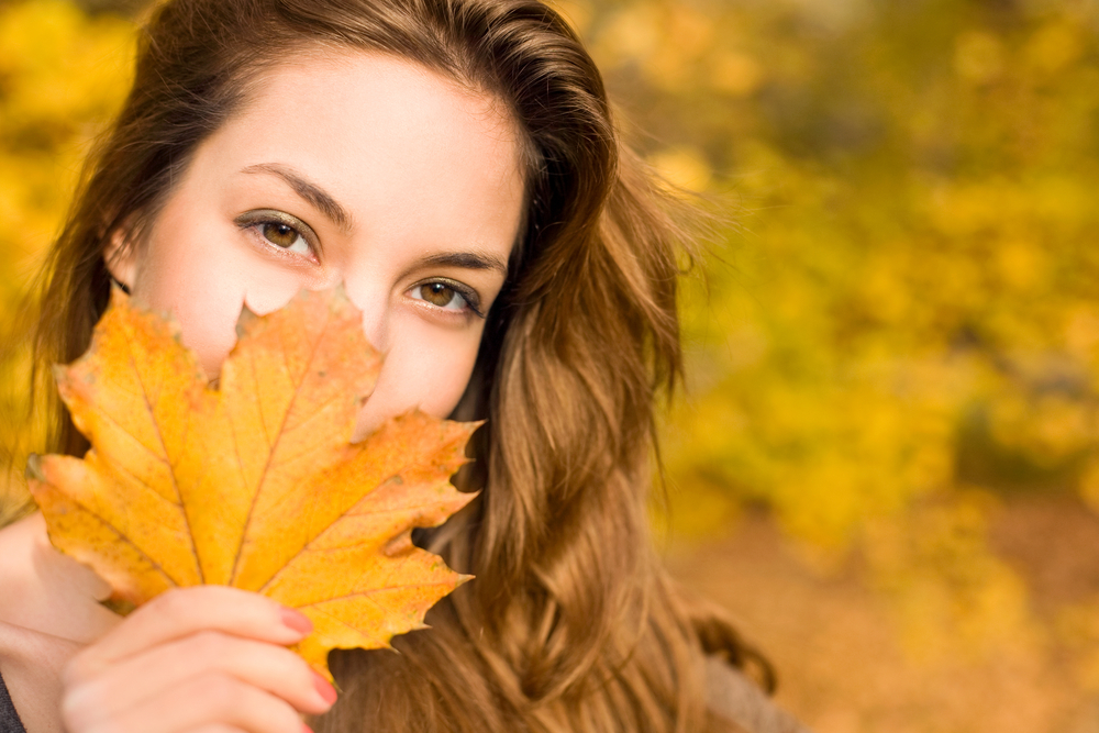 Woman hiding behind a yellow leaf in the fall.