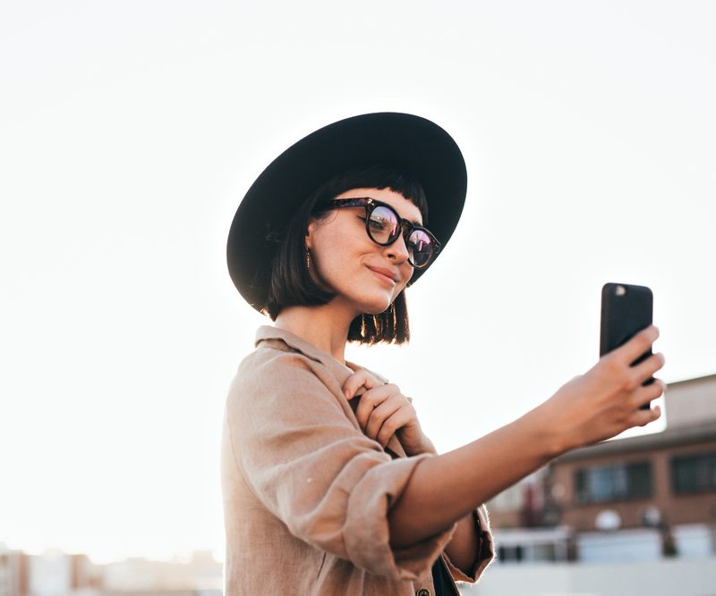 Woman taking a selfie (self photo) in fashionable outfit.