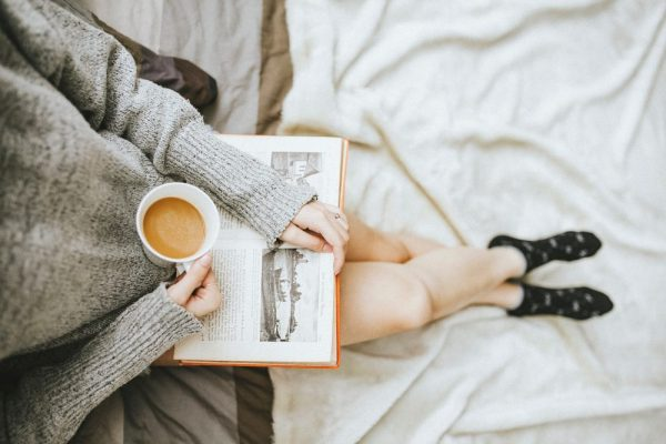 Woman enjoying a cup of coffee while reading a book.