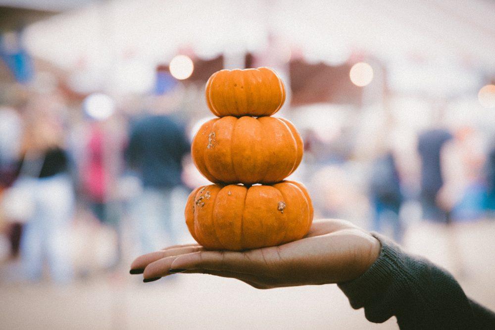 Stack of pumpkins in someones hand.