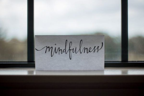 Mindfulness spelled out on a piece of paper by a window.