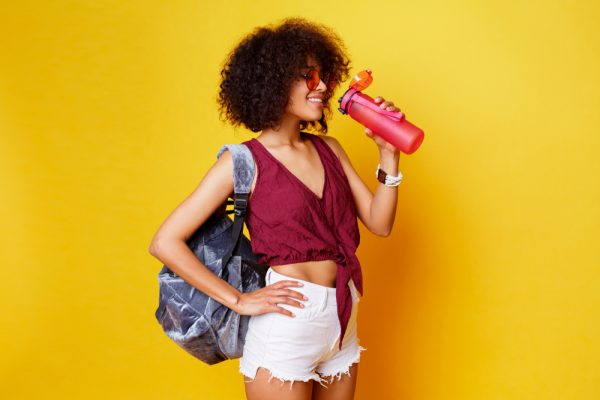 Woman drinking from a pink water bottle.