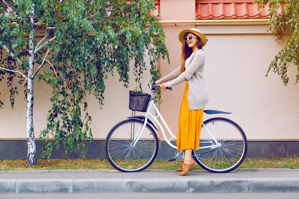Woman in a yellow dress and big hat on a bike.