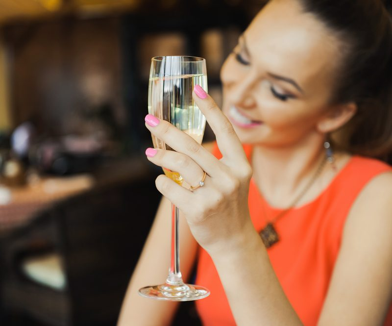 Woman in an orange dress holding a glass of champagne.