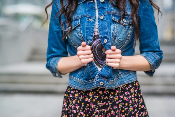 Woman opening her jean jacket.