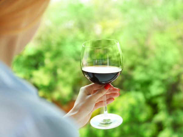 Woman with red nails holding a glass of wine.