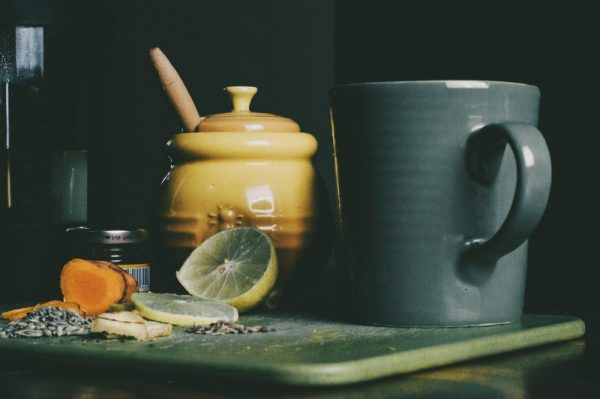 Kitchen counter, cutting board with lemon, a mug, and a honey pot.