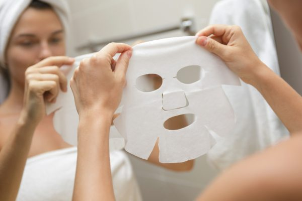 Woman holding a sheet mask out infront of her for skin care.
