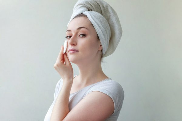 Woman using cotton pad to cleanse face.