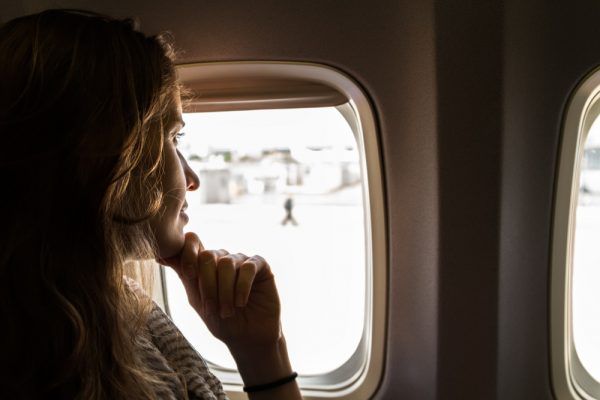 Woman on a flight by the window seat while traveling.